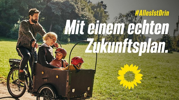 Wahlplakat Grüne zeigt Mann, der Frau im Kleid und 2 Kinder kutschiert